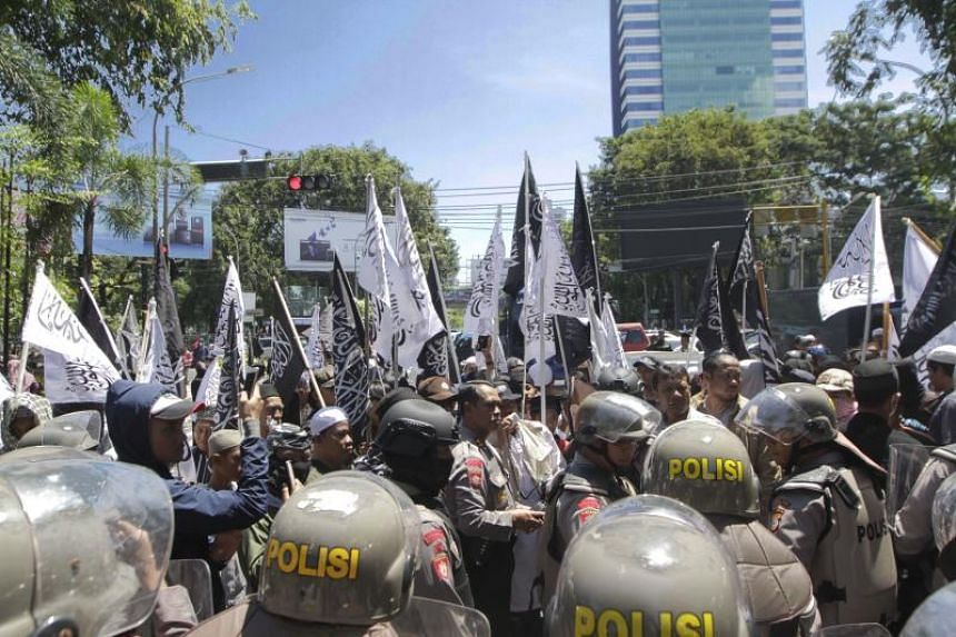 Indonesian policemen guard members of the radical Hizb ut-Tahrir Indonesia during a rally on April 16, 2017.