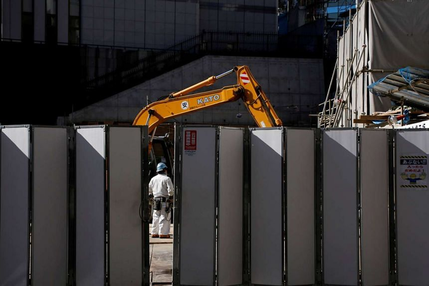 A worker is pictured next to heavy machinery at a construction site in Tokyo's business district, Japan.