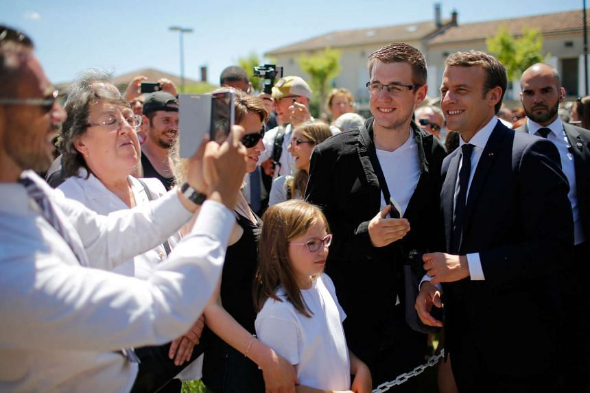 """French President Emmanuel Macron (right) posing for a """"selfie"""" after attending a ceremony to commemorate the 73rd anniversary of the Oradour-sur-Glane massacre, as part of a visit to the martyrs village of Oradour-sur-Glane, on June 10, 2017."""