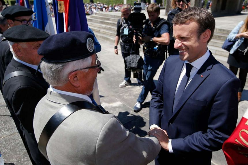 French President Emmanuel Macron (right) shakes hands with veterans associations members after a ceremony to commemorate the 73rd anniversary of the Oradour-sur-Glane massacre, as part of a visit to the martyrs village of Oradour-sur-Glane, on June 1