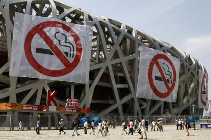 Large anti-smoking banners hang on the exterior of the Bird's Nest stadium as tourists walk by in Beijing, China, May 30 2015.