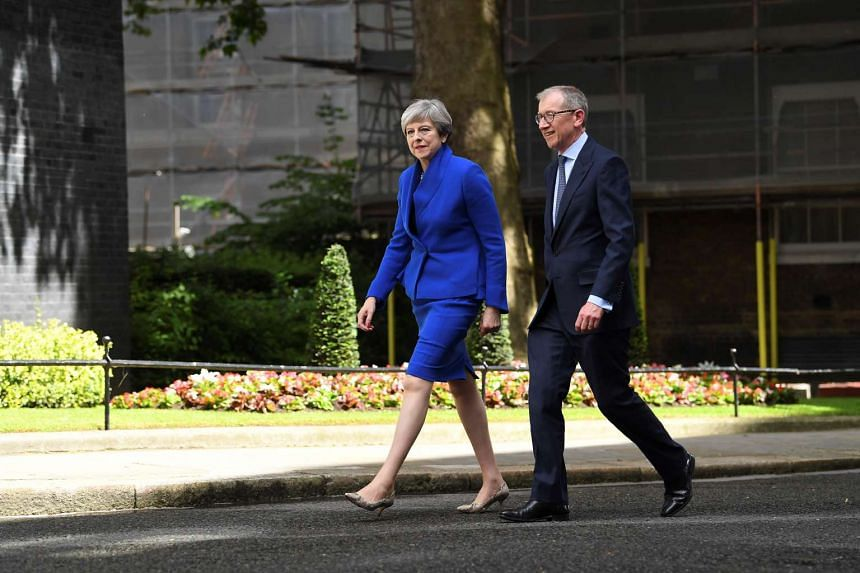Britain's PM and leader of the Conservative Party Theresa May, accompanied by her husband Philip, arrives to deliver a statement in central London, on June 9, 2017