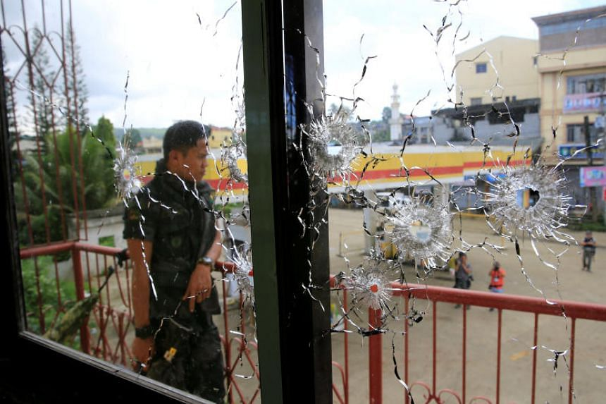 A policeman stands on guard behind a window full of bullet holes as government soldiers assault the Maute group in Marawi City on May 31, 2017.