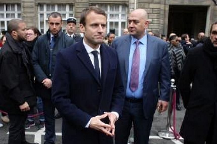 Emmanuel Macron (centre), prior to his election as France's president, attends a ceremony honouring the policeman killed on the Champs Elysees, on April 25, 2017.