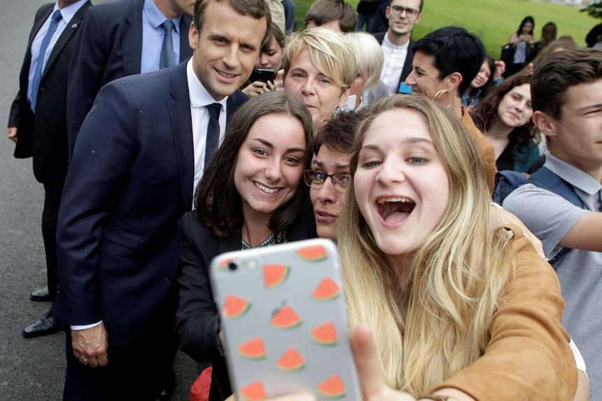 Students take a selfie photo with French President Emmanuel Macron (rear left) during a visit to Verneuil-sur-Vienne, France on June 9, 2017.