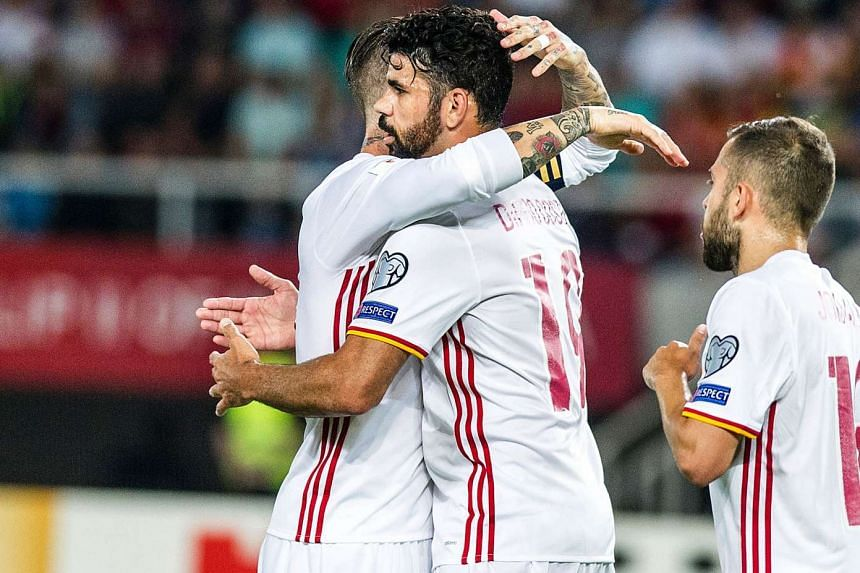 Spain's Diego Costa (second from left) celebrates with teammate Sergio Ramos (left) after scoring a goal during the World Cup qualifier on June 11, 2017.