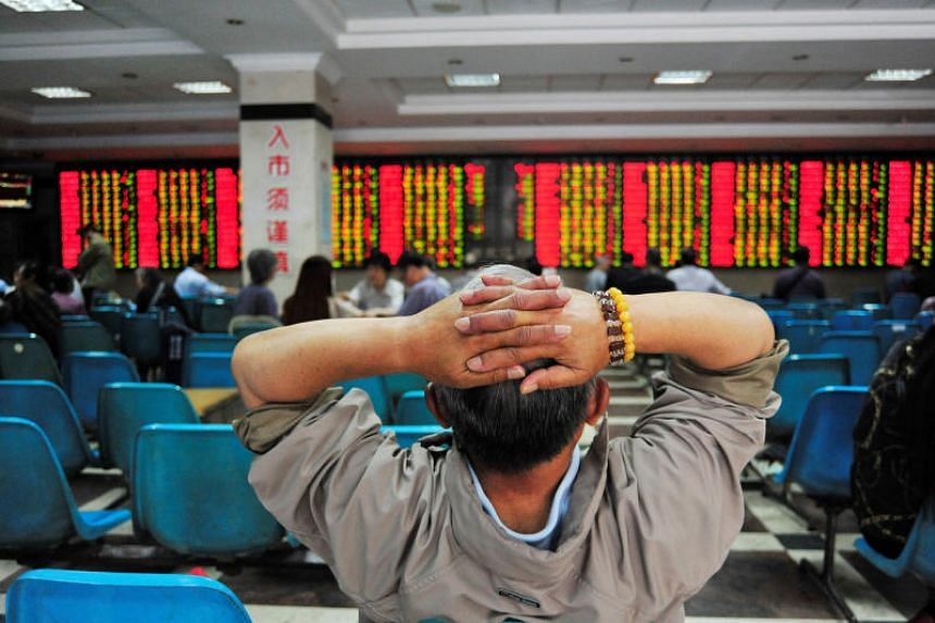 An investor looks at an electronic board showing stock information at a brokerage house in Nanjing, China.