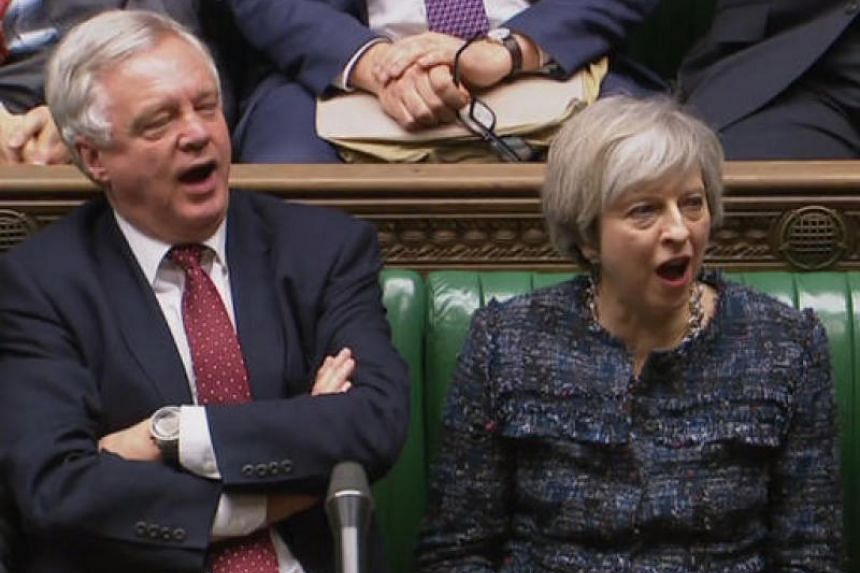 In a still image taken from footage broadcast by the UK Parliamentary Recording Unit (PRU) on Feb 8, 2017, British Prime Minister Theresa May and British Secretary of State for Exiting the European Union (Brexit Minister) David Davis shout 'aye' in t