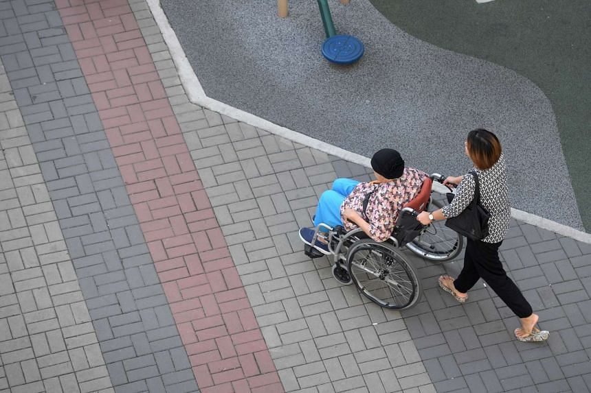 A caregiver pushing an elderly woman on a wheelchair.