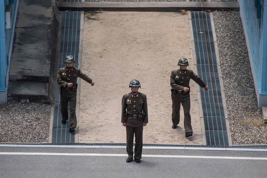 Korean People's Army (KPA) soldiers stand guard at the military demarcation line separating North and South Korea, at the Joint Security Area (JSA) near Kaesong on the North Korean side of the border on June 2, 2017.
