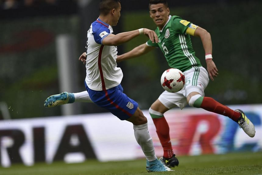 US' player Bobby Wood (left) vies with Mexico's Hector Moreno during their 2018 FIFA World Cup Concacaf qualifier football match, in Mexico City, on June 11, 2017.