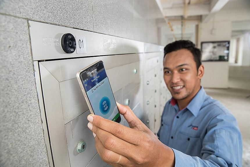 A Singapore Post employee demonstrating the use of the SmartPost app on a smartphone at a near-field communication (NFC) tag. By March 2019, more than 50,000 letterbox nests will be tagged with NFC. SingPost said it plans to tag every letterbox nest