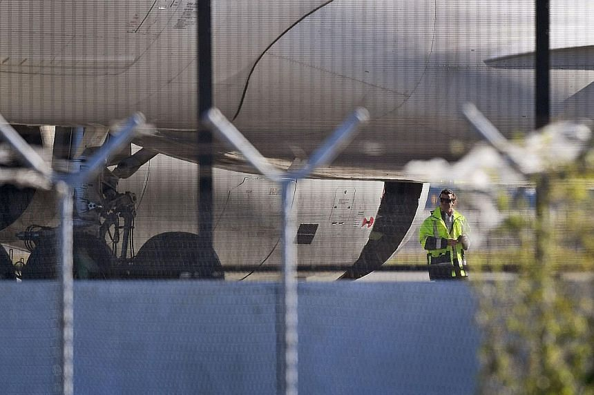 The China Eastern Airbus A-330 plane with the damaged engine cowling at Sydney Airport yesterday. The aircraft made an emergency landing after a huge hole appeared in an engine casing.