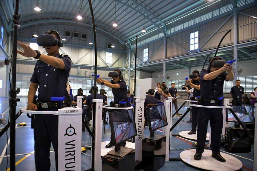 Police officers demonstrating simulation training on omni-directional treadmills with head-mounted displays which enable the users to move around in a virtual world in the Bedok Police Division on June 12, 2017.