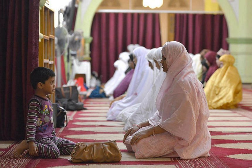 A child watches as Muslim women gather to pray after breaking fast at the Sultan Mosque on July 21, 2012.