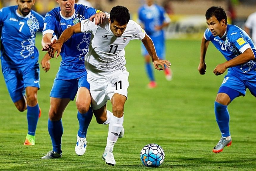 Iran's Vahid Amiri (centre) in action against Uzbekistan during the World Cup qualifying match on June 12, 2017.