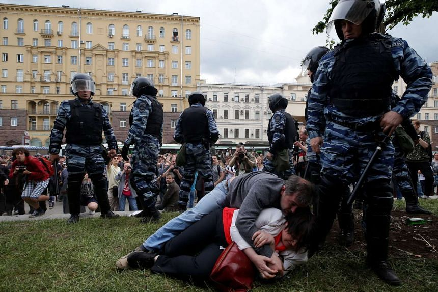 Activist Yulia Galyamina and her husband Nikolai Tuzhilin lie on the ground next to riot police during in Moscow on June 12, 2017.