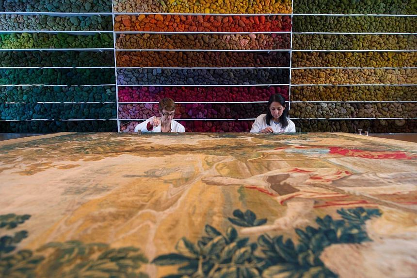 Specialist restorers work on an old tapestery at the Royal Manufacturers De Wit in Mechelen on April 25, 2017.