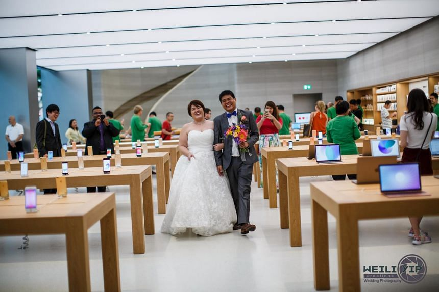 "The couple having a ""walk down the aisle"" in the midst of customers and staff in the Apple store in Orchard Road."