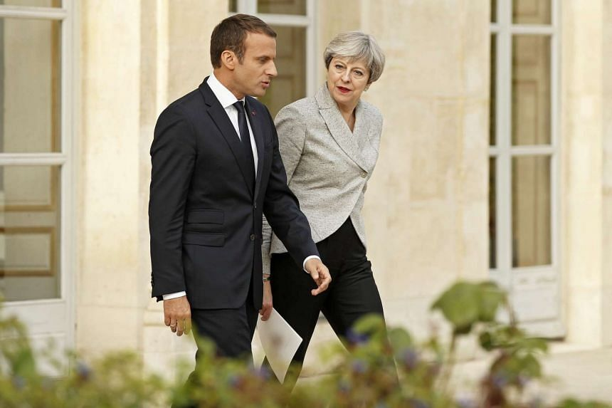 Macron (left) and May arrive to deliver joint statements to the press at the Elysee Palace in Paris,.