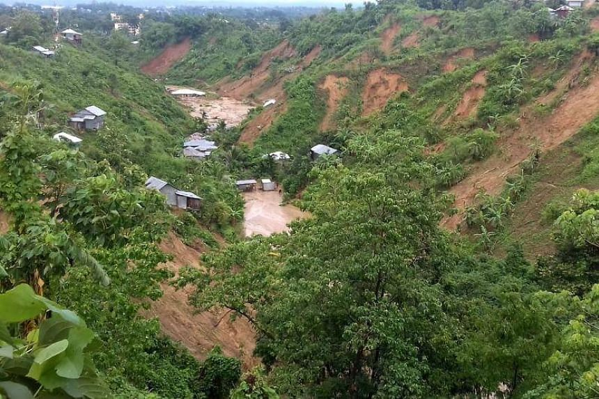 This general view shows dwellings under mud after a landslide in Rangamati on June 13, 2017.