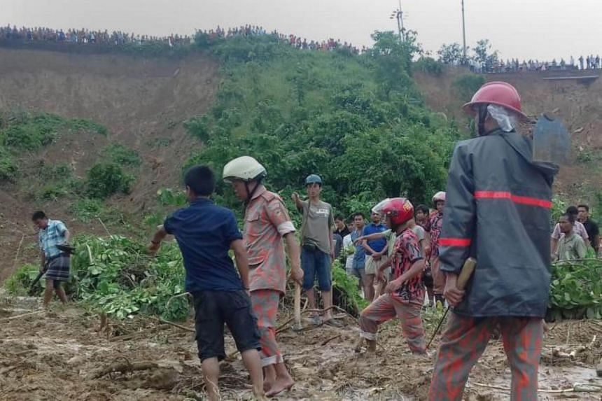 Bangladeshi firefighters and volunteers are watched by bystanders as they search for bodies after a landslide in Rangamati on June 13, 2017.
