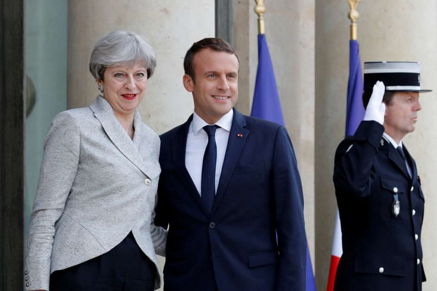 Macron greets Britain's Theresa May (left) before a working dinner at the Elysee Palace in Paris.