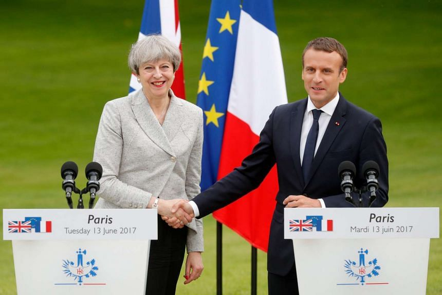 Macron (right) and May shake hands after speaking to the press at the Elysee Palace in Paris.