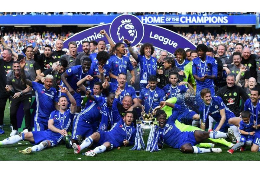 Chelsea's players gather on the pitch with the English Premier League trophy, as they celebrate their league title win at the end of the Premier League football match between Chelsea and Sunderland at Stamford Bridge in London on May 21, 2017.