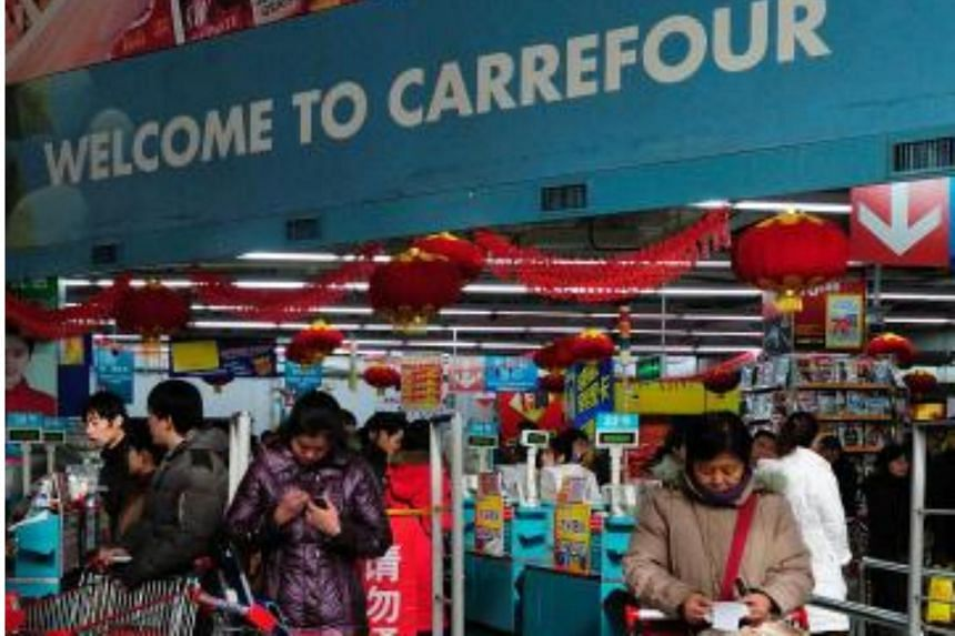 A shopper checks her bill (right) at a Carrefour store in Beijing on Jan 27, 2011.