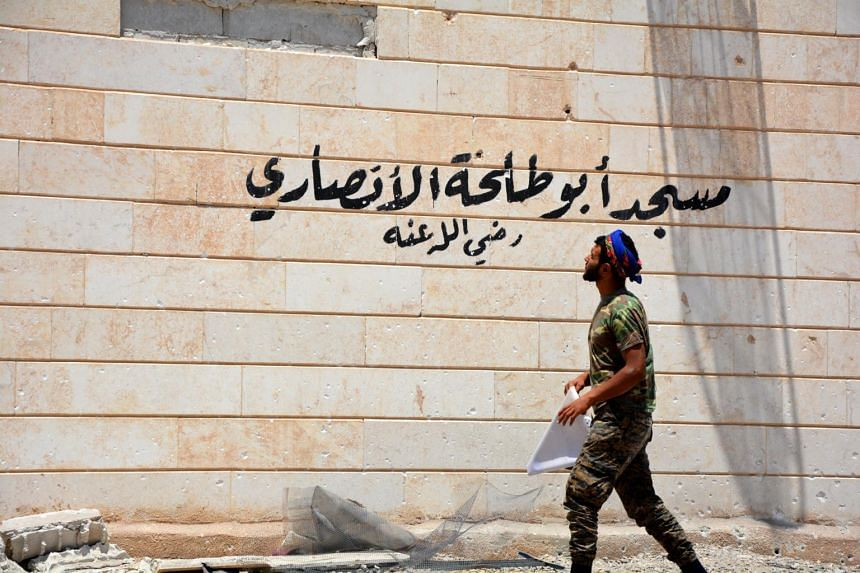 A man looks on a mosque with the words 'Abo Talha al-Ansary Mosque's' written on it, at Raqqa city, Syria on June 11, 2017