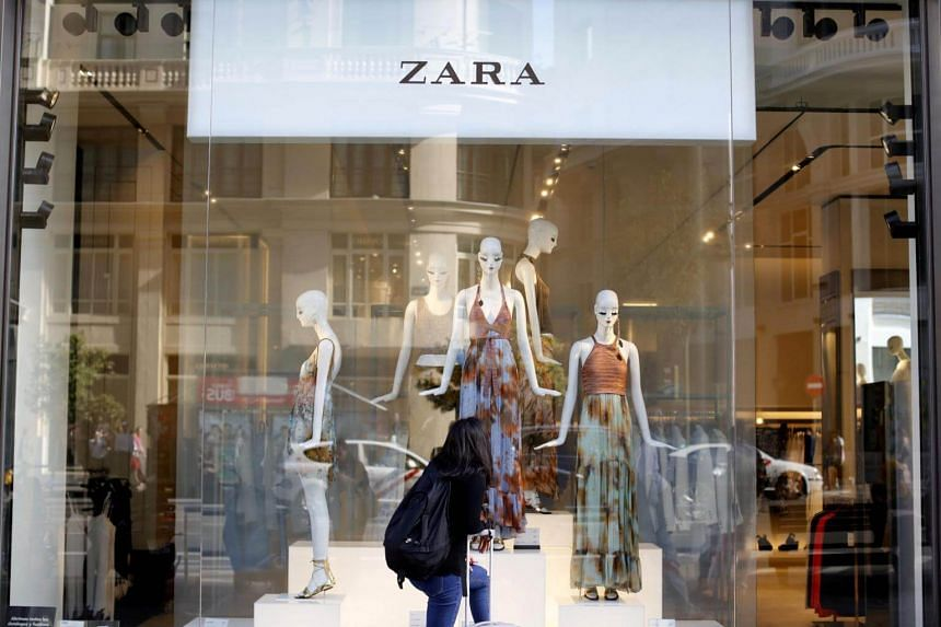 A woman looks at a display window in a Zara store in Madrid, Spain, on June 15, 2016.