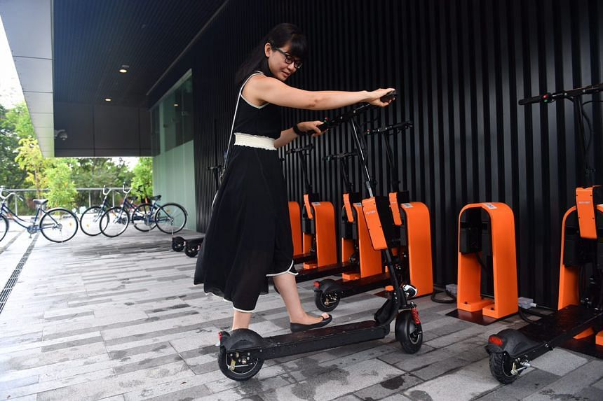 Ms Vivian Goi, 40, from Ascendas Singbridge, demonstrates taking the e-scooter out from the docking station.