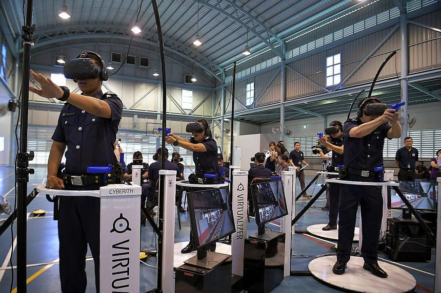 Police officers on omni-directional treadmills demonstrating simulation training with head-mounted displays at the Bedok Police Division on Monday. The set-up enables users to move around in a virtual world. Such training is increasingly becoming imp