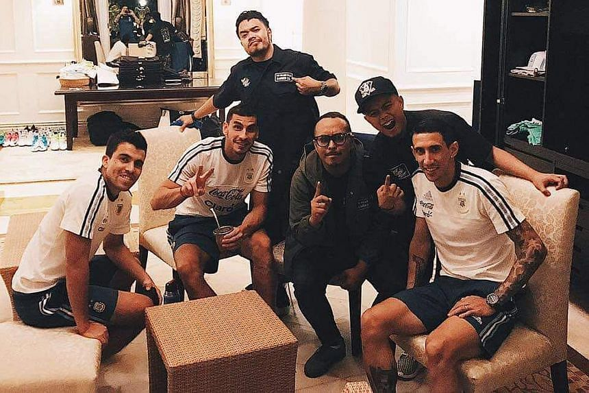 Barbers from The Golden Rule Barber Co. posing with Argentina winger Angel di Maria and his team-mates after giving several Argentina players a haircut at the Fullerton Hotel yesterday.