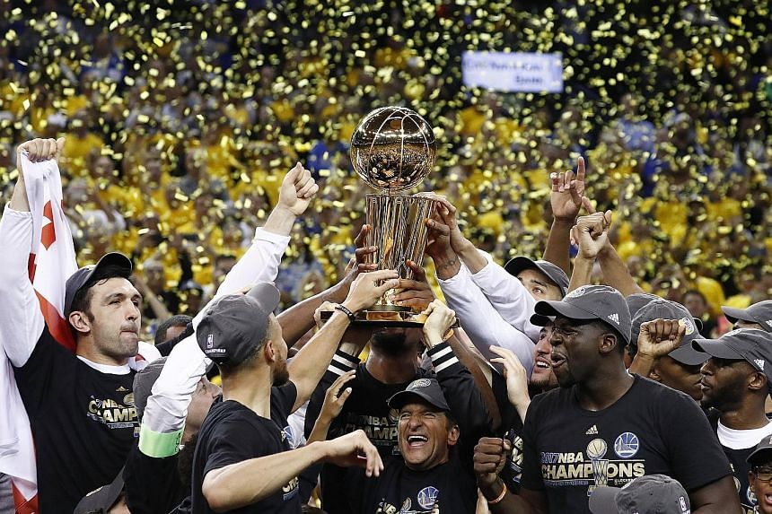The Golden State Warriors celebrate with the Larry O'Brien trophy after their 129-120 victory against the Cleveland Cavaliers in Game Five to regain the NBA championship with a 4-1 series win..