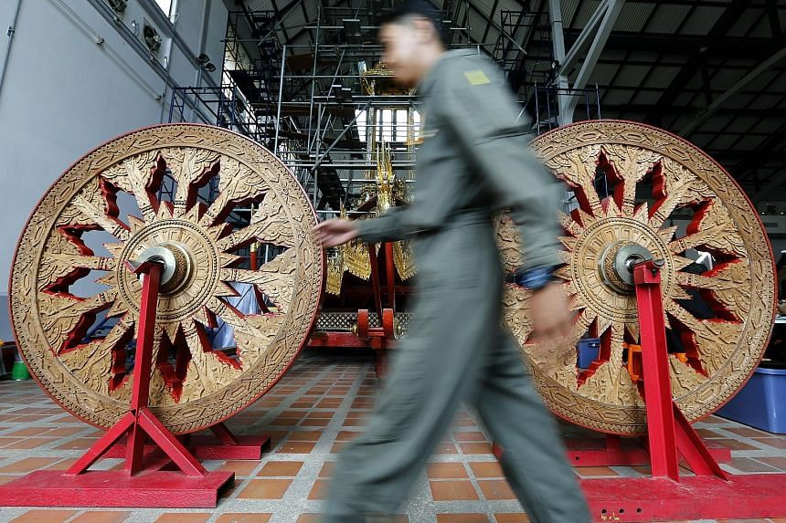 These wooden angels (above) and wheels (right), as seen yesterday at the National Museum in Bangkok, will be part of the Royal Chariot to be used for the late Thai King Bhumibol Adulyadej's funeral ceremony. The Royal Chariot (right, in background)