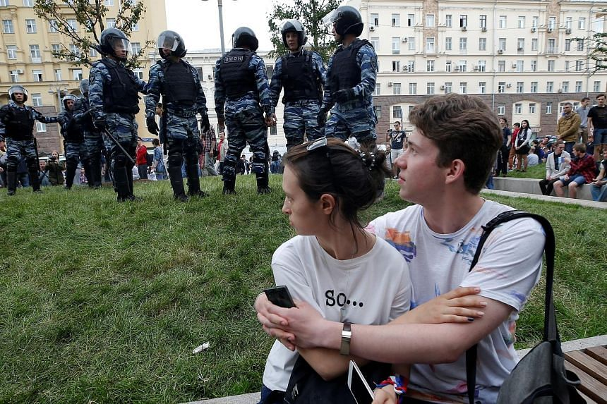 Riot police on guard in Moscow during Monday's protests across Russia, called by Kremlin critic Alexei Navalny (above), who was arrested before he even made it to a protest site. He was sentenced to 30 days in jail.