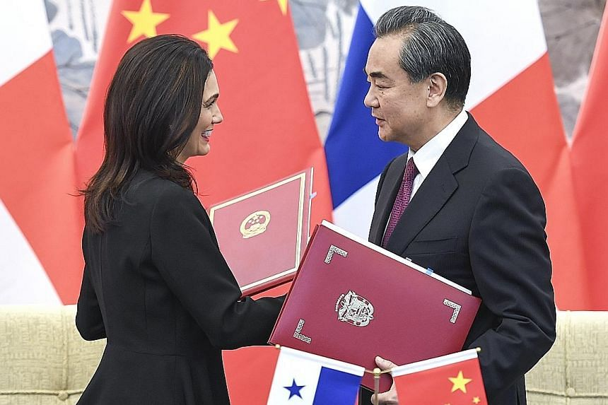 Panamanian Vice-President and Foreign Minister Isabel Saint Malo exchanging documents with Chinese Foreign Minister Wang Yi in Beijing yesterday after signing a joint communique on establishing diplomatic relations.