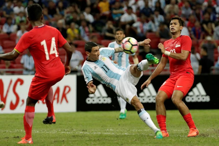 Argentina's Angel Di Maria in action with Singapore's Zulfahmi Arifin.