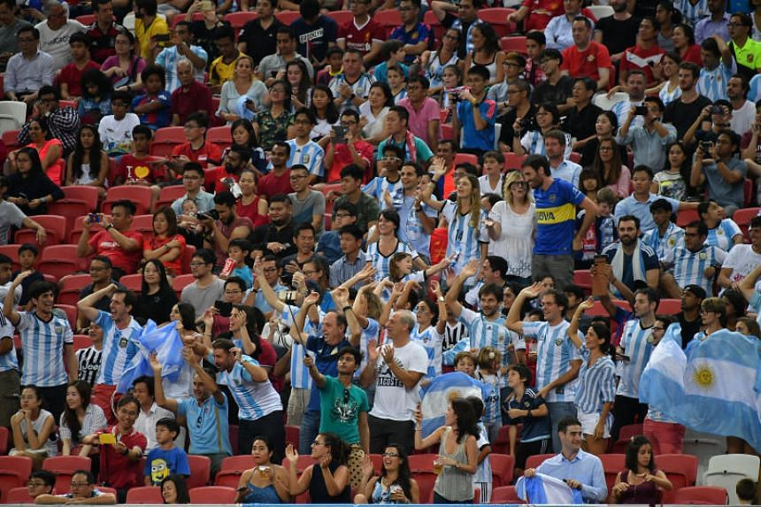 Fans cheering for their team at the Singapore versus Argentina football match at the National Stadium, on June 13, 2017.