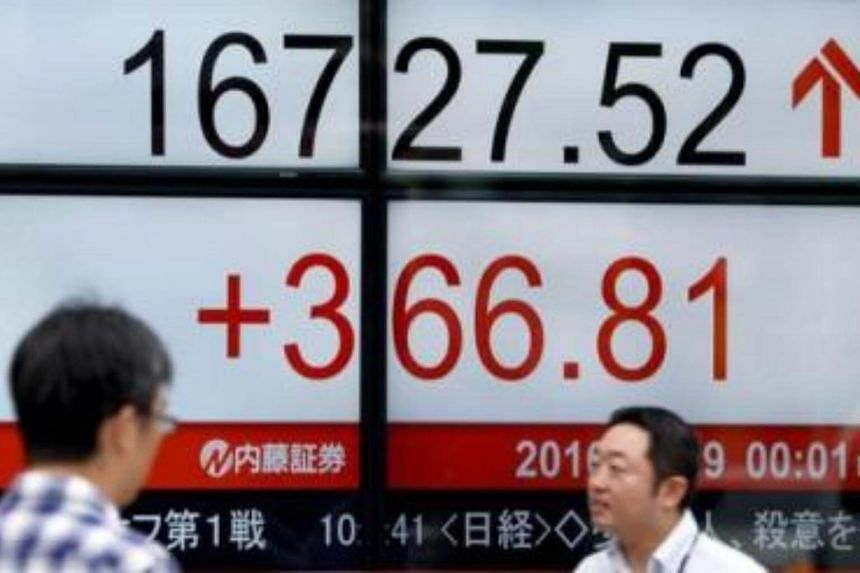 People walk past an electric quotation board flashing the Nikkei key index of the Tokyo Stock Exchange (TSE) in front of a securities company.