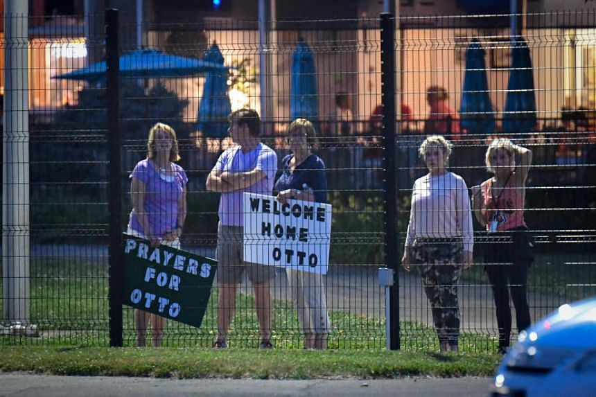 Local residents hold signs of support to welcome home Otto Warmbier at Lunken Airport in Cincinnati.