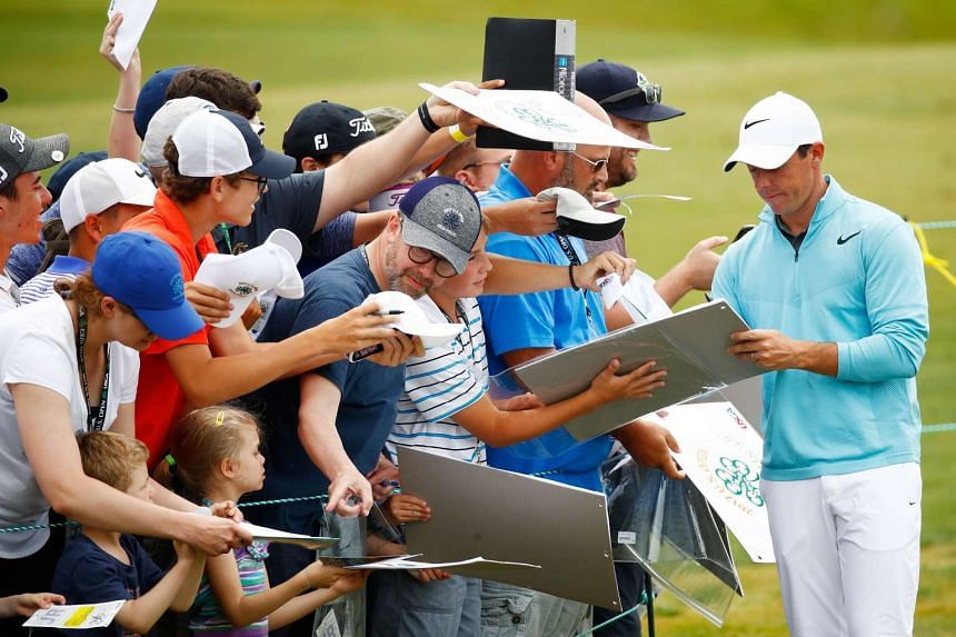McIlroy signs autographs during a practice round prior to the 2017 US Open.