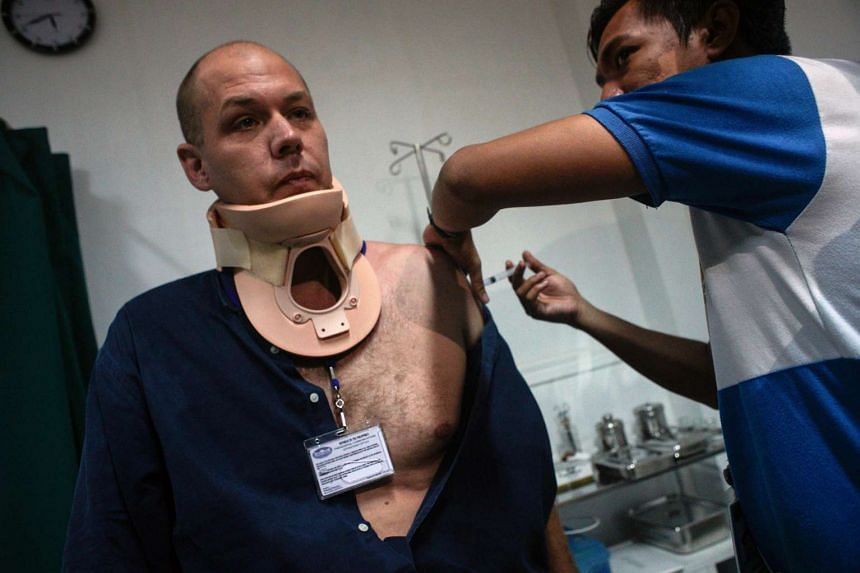 Australian journalist Adam Harvey (left) receives medical treatment from a gunshot wound as fighting between Islamist militants and government forces continues in Marawi City, Mindanao Island, Philippines, June 15, 2017.
