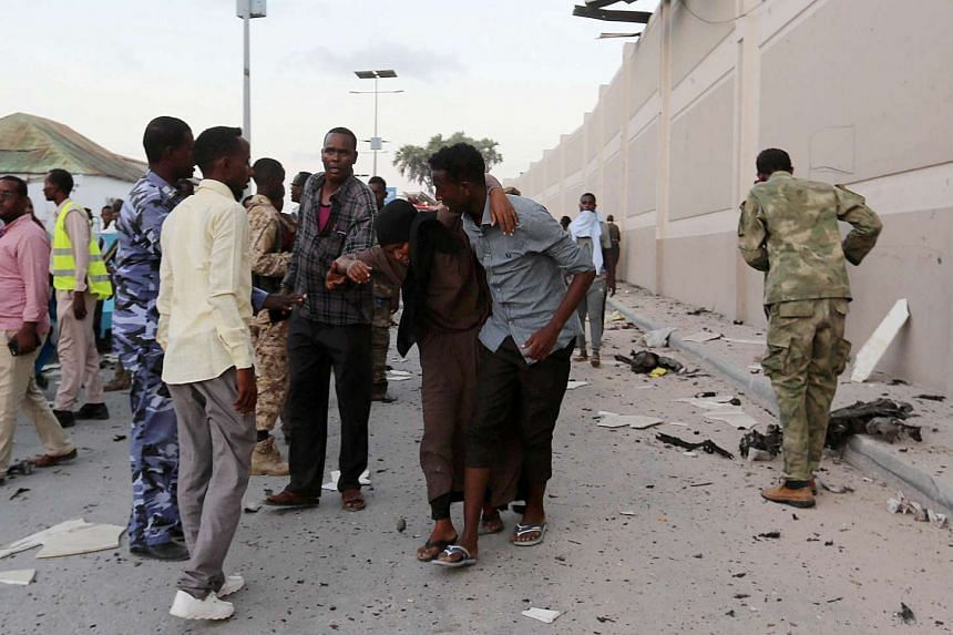 People help a woman injured by a blast in Mogadishu, on May 24, 2017.