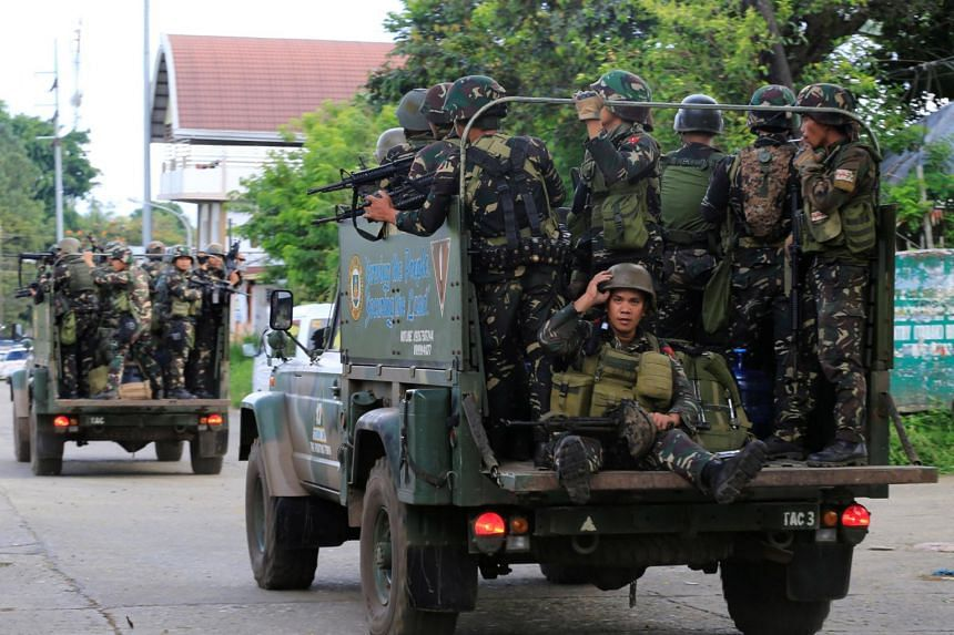 Government soldiers are seen onboard military vehicles as they continue their assault against insurgents from the Maute group, who have taken over large parts of the Marawi City, in Philippines on June 13, 2017.