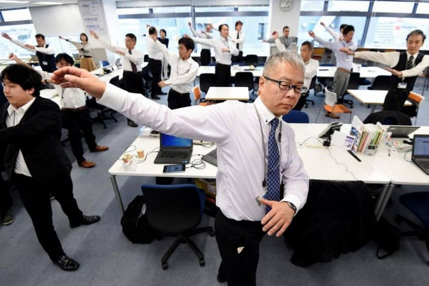 Employees of an information technology company exercising together in their office after lunchtime in Tokyo.
