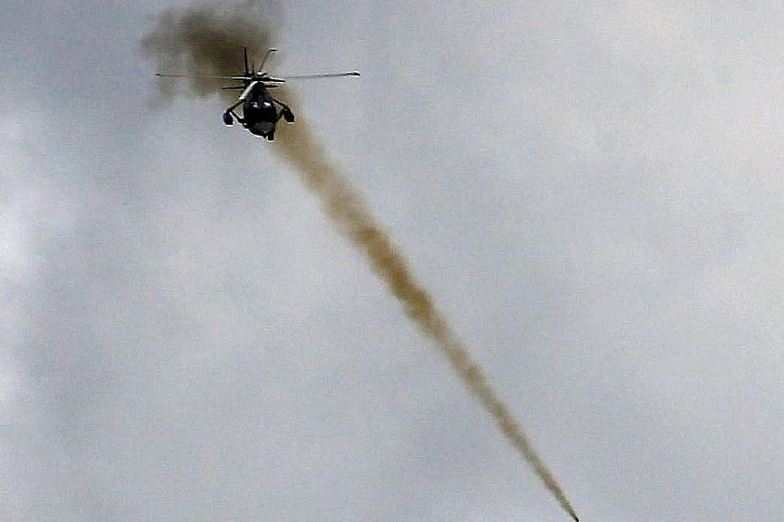 A Philippine Air Force helicopter launching a rocket as government troops continued their assault on Marawi yesterday.