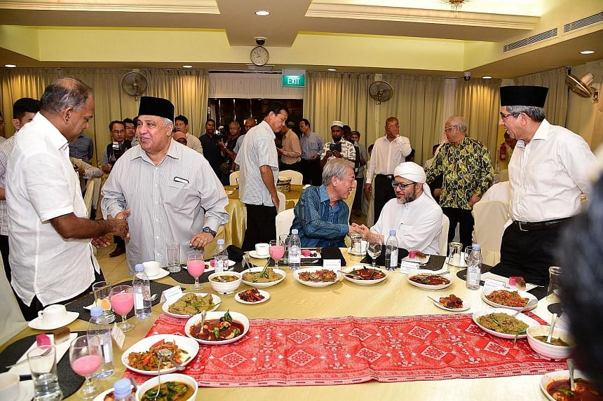 At the breaking of fast session organised by the Religious Rehabilitation Group (RRG) and the Khadijah Mosque in Geylang yesterday were (from left) Minister for Home Affairs and Law K. Shanmugam, RRG co-chair Ali Mohamed, Acting Prime Minister Teo Ch